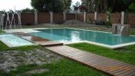 piscina con desborde perimetral, fuente con chorros y cascada laminar